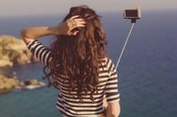 Woman takes selfie at cliff's edge with water in background. Photo via Shutterstock