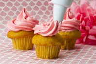 Person icing a cupcake with pink icing from a pipette. Photo by Shutterstock