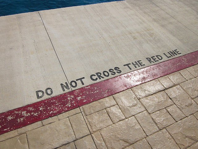 do not cross the red line notice painted at side of swimming pool