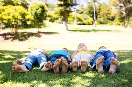 Children playing outside, lie barefoot on grass. Photo by Shutterstock