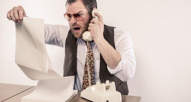 Angry man yelling on phone while reading vintage printer paper report. Photo by SHutterstock