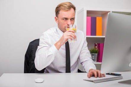Man types something into Mac while sipping a glass of lemon water. Not a brilliant idea. Photo by SHutterstock