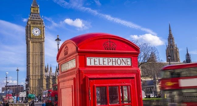 London - Iconic Red telephone box with Big Ben at the background and blue sky - UK, England. Photo by Shutterstock