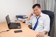Exhausted looking business man on phone in from of laptop. Photo by Shutterstock