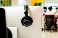 Man sits at workstation while the nuext cubicle remains empty, with the headphones hung up on the cubicle wall. Photo by Shutterstock