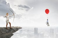 Businesswoman shoots arrow from cliff at balloon holding up rival... Bit silly conceptual art. Photo by Shutterstock