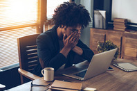 Embarrassed/exhausted man sits in front of laptop in hipstery office. Photo by Shutterstock