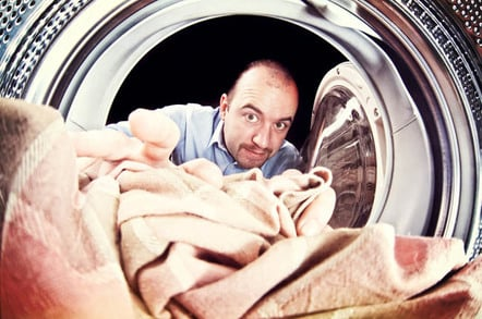 Man loads in blanket into the washing machine. Photo by Shutterstock
