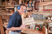"Man in woodworking workshop wearing headphones raises sign that reads ""I'm not listening"". Photo by Shutterstock"