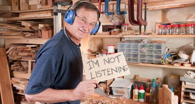 """Man in woodworking workshop wearing headphones raises sign that reads """"I'm not listening"""". Photo by Shutterstock"""