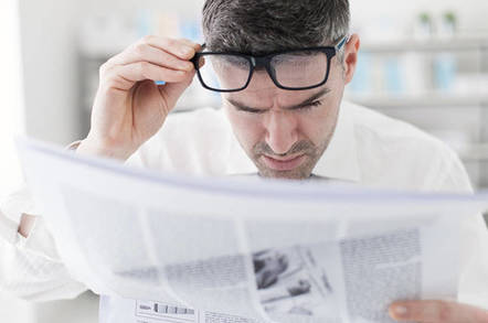 Man reading newspaper with glasses on his head