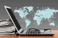 Laptop leaning against a stack of news papers in front of a world map illustration