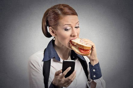 Lady eating a sandwich checking her mobile phone
