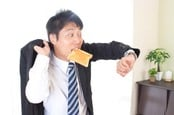 Man eats toast while looking at watch, clearly late for something. Photo by Shutterstock