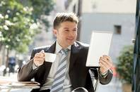 Man in a suit drinking tea out doors reading from his tablet