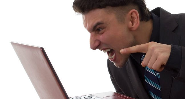 An angry man gesticulates at his laptop screen. Photo by Shutterstock