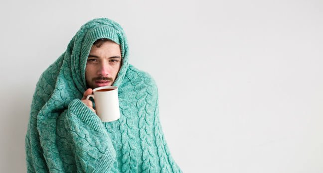 Man wrapped in turqouise cable-knit blanket sips from hot drink - is clearly ill. Photo by Shutterstock