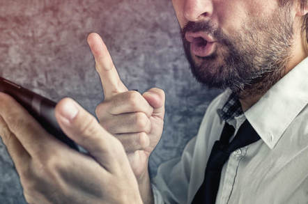 A man talks angrily into his mobile. Photo via Shutterstock