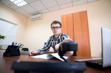 Man hangs up desk phone after a clearly irritating call. Photo by Shutterstock