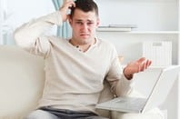 Confused/annoyed looking man looks irritated during outage. Photo via Shutterstock