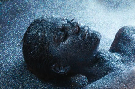 """""""New and shiny"""" person lies with eyes closed, covered in grey glitter. Photo by Shutterstock"""