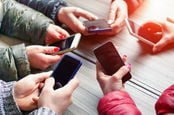 A group of people hold out mobile phones in a circle. Photo by Shutterstock