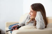 Woman watches TV with cat, uses remote to change channel. Photo by Shutterstock