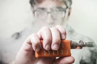 Man with a vaper apparatus - face obscured by smoke/vapour. Photo by Shutterstock