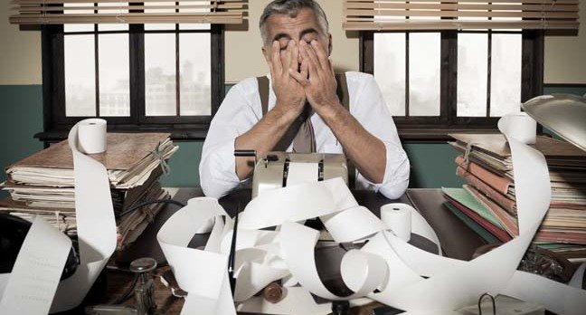 Frustrated accountant puts head in hands. Photo by Shutterstock