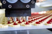 Conveyor belt production of jam-topped biscuits. Photo by Shutterstock