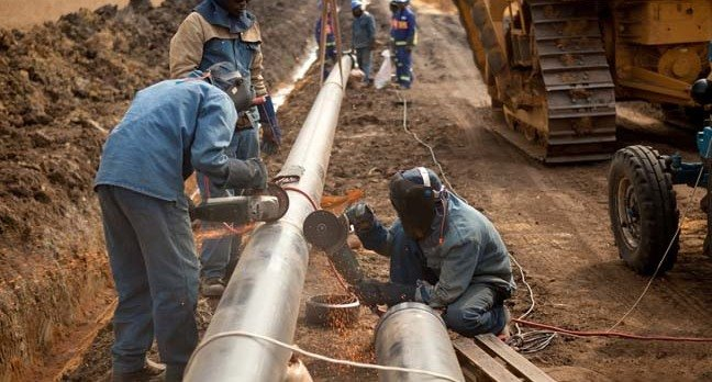 Welders wearing protective clothing fixing welding and grinding industrial construction oil and gas or water and sewerage plumbing pipeline outside on site. Photo by Andrea Slatter/Shutterstock