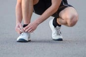 Man ties laces on running shoe pre-jog. Photo by Shutterstock