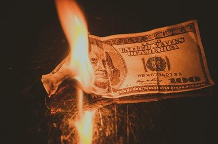 Burning money, photo via Shutterstock