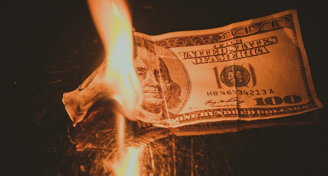 Burning money, photo via Shutterstock