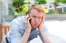 Man exasperated after being on hold for a long period of time. Photo by Shutterstock