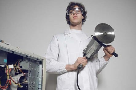 Techie wields circular saw while standing over the innards of a workstation. Photo by Shutterstock