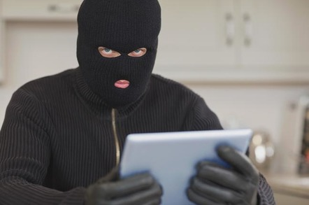 Burglar sits in kitchen with stolen tablet. Photo by Shutterstock