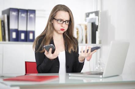 woman tries to choose between two smartphones