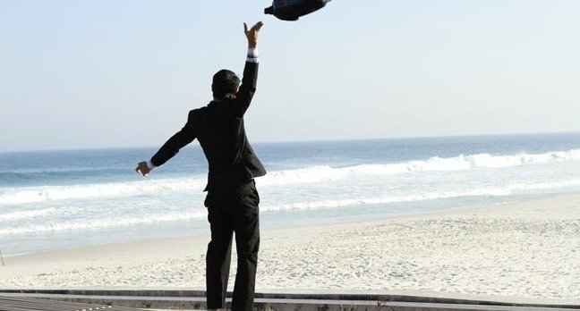 Man throws briefcase in the air happily on the beach. Photo by Shutterstock