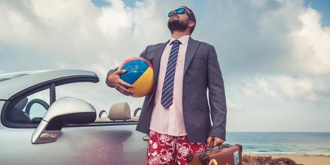 """Guy in shirt and tie visits the beach. wearing """"beach business-casual"""". Photo by Shutterstock"""