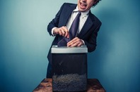 Man shreds documents. Photo by Shutterstock
