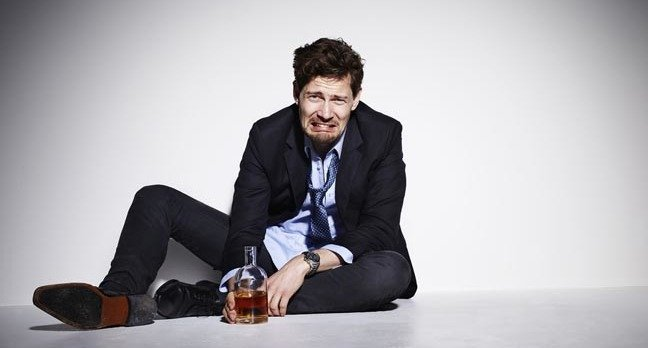 Upset man in suit and drinking liquor. Photo by Shutterstock