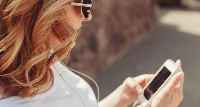 Woman uses headphones with her iPhone. Photo by Shutterstock