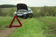 A car pulled over near a hazard sign on a country road. Photo by Shutterstock