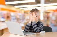 Child in shock in front of computer. Photo by Shutterstock