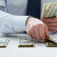 Man in suit counts out piles of dollars. Photo via Shutterstock