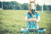 Woman in horse mask takes a selfie. Photo by Shutterstock