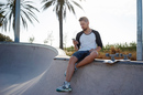 Man checks mobile while sitting on skateboard ramp. Photo by Shutterstock