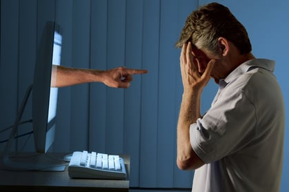 Cheesy pic of man holding face in shame as accusatory finger emerges from display. Photo via Shutterstock