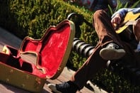 Street musician busks for coins. Photo by Shutterstock